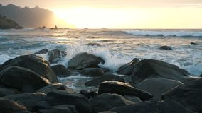 Le onde di oceano si schiantano sulle rocce e sullo spruzzo alla bella luce del tramonto alla spiaggia di Benijo in Tenerife, iso archivi video