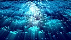 Le onde di oceano subacquee si increspano e scorrono con i raggi luminosi