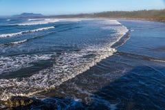 Le onde drammatiche spazzano sopra Long Beach, Tofino, BC immagini stock