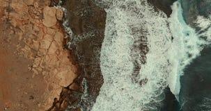 Le onde enormi si rivoltano uno un altro e rottura sulla costa di pietra video d archivio