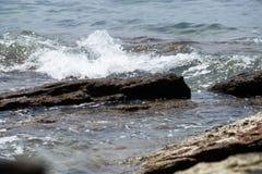 Le onde hanno battuto le rocce fotografie stock