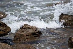 Le onde hanno battuto le rocce immagine stock