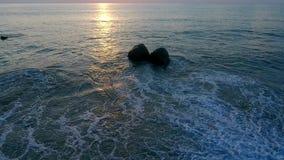 Le onde pigre ed una coppia di roccia stock footage