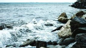 Le onde si battono contro le rocce sulla riva archivi video
