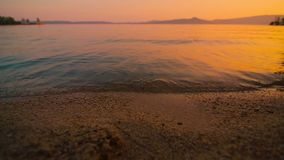 Le onde si battono lentamente contro la spiaggia sabbiosa del lago al bello tramonto archivi video