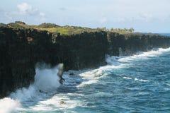 Le onde si schiantano lungo le scogliere nere della roccia della lava Immagine Stock