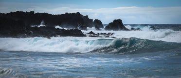 Le onde si schiantano lungo le scogliere nere della roccia della lava immagine stock libera da diritti