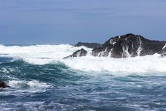 Le onde si schiantano sulle rocce vulcaniche Immagini Stock Libere da Diritti