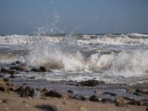 Le onde spruzzano e rotolano su una spiaggia sabbiosa fotografie stock