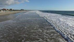 Le onde spumose avvolgono delicatamente al litorale stock footage