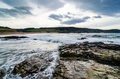 Le onde sulla costa in Verdicio tirano in Asturie Spagna Mare mosso in una spiaggia vergine con le rocce e schiuma alla sera Fotografie Stock Libere da Diritti