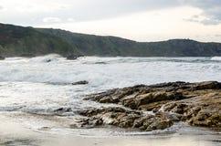 Le onde sulla costa in Verdicio tirano in Asturie Spagna Mare mosso in una spiaggia vergine con le rocce e schiuma alla sera Fotografia Stock