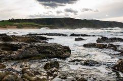 Le onde sulla costa in Verdicio tirano in Asturie Spagna Mare mosso in una spiaggia vergine con le rocce e schiuma alla sera Fotografie Stock
