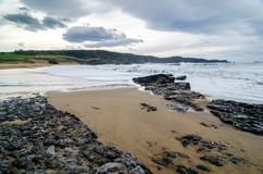 Le onde sulla costa in Verdicio tirano in Asturie Spagna Mare mosso in una spiaggia vergine con le rocce e schiuma alla sera Fotografia Stock Libera da Diritti