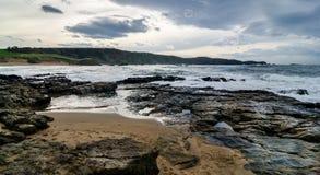 Le onde sulla costa in Verdicio tirano in Asturie Spagna Mare mosso in una spiaggia vergine con le rocce e schiuma alla sera Immagine Stock