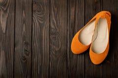 Le ` orange s de femmes chausse des ballerines sur le fond en bois Images stock