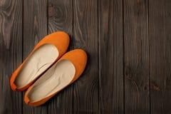 Le ` orange s de femmes chausse des ballerines sur le fond en bois Image libre de droits