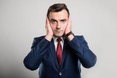 Le orecchie attraenti della copertura dell'uomo di affari gradiscono il gesto sordo fotografia stock