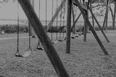 Le oscillazioni abbandonate vuote in bianco e nero in un parco locale riflettono la nostra infanzia dimenticata immagine stock libera da diritti