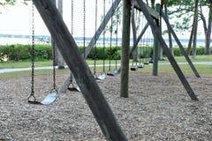 Le oscillazioni abbandonate vuote in un parco locale riflettono la nostra infanzia dimenticata immagini stock
