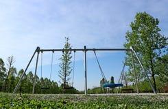 Le oscillazioni dei bambini inossidabili in un parco pubblico vuoto fotografia stock libera da diritti