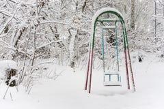 Le oscillazioni dei bambini nel parco di inverno fotografia stock