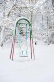 Le oscillazioni dei bambini nel parco di inverno fotografia stock libera da diritti