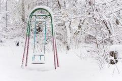Le oscillazioni dei bambini nel parco di inverno fotografie stock libere da diritti