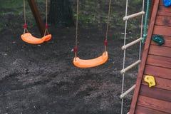 le oscillazioni dei bambini sulle catene nel campo da giuoco contro un fondo scuro la bascula arancio dei bambini terra nera scur fotografia stock