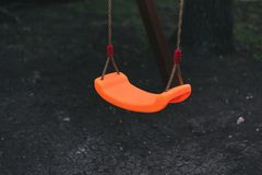 le oscillazioni dei bambini sulle catene nel campo da giuoco contro un fondo scuro la bascula arancio dei bambini terra nera scur immagine stock