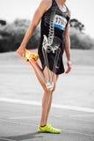 Le ossa evidenziate dell'atleta equipaggiano l'allungamento sulla pista di corsa Immagine Stock