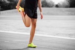 Le ossa evidenziate dell'atleta equipaggiano l'allungamento sulla pista di corsa Fotografia Stock Libera da Diritti
