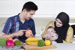 Le père épluche la pomme pour son épouse et bébé Photos libres de droits