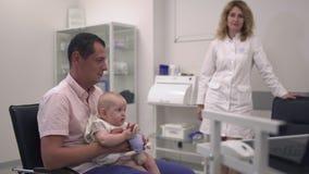 Le père affectueux tient sa petite fille dans des bras dans l'hôpital banque de vidéos
