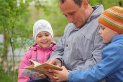 Le père affiche le livre pour des gosses, orientation sur la petite fille Photo libre de droits