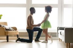 Le père africain a obtenu vers le bas sur des mains d'une de genou fille de prise photo stock