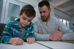 Le père aidant le fils dans le sien étudie Photos libres de droits