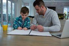 Le père aidant le fils dans le sien étudie Photographie stock libre de droits