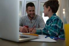 Le père aidant le fils dans le sien étudie Photo stock