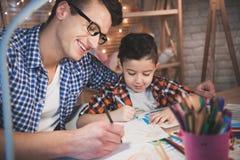 Le père aide le fils à dessiner avec des crayons et des marqueurs de couleur sur le papier la nuit à la maison Images stock