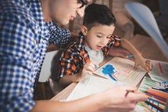 Le père aide le fils à dessiner avec des crayons et des marqueurs de couleur sur le papier la nuit à la maison Image stock