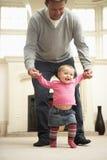 Le père aide le descendant de chéri avec la marche Photographie stock