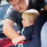 Le père aide son fils d'enfant en bas âge à attacher la ceinture sur le siège de voiture Images libres de droits