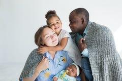 Le père aimant couvre sa famille de plaid Famille multi-ethnique heureuse Valeurs familiales photos stock
