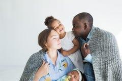 Le père aimant couvre sa famille de plaid Famille multi-ethnique heureuse Valeurs familiales photo stock