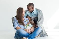 Le père aimant couvre sa famille de plaid Famille multi-ethnique heureuse Valeurs familiales photographie stock