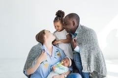 Le père aimant couvre sa famille de plaid Famille multi-ethnique heureuse Valeurs familiales image stock