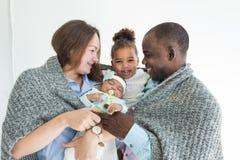Le père aimant couvre sa famille de plaid Famille multi-ethnique heureuse Valeurs familiales image libre de droits
