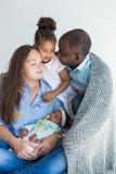 Le père aimant couvre sa famille de plaid Famille multi-ethnique heureuse Valeurs familiales images stock