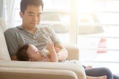 Le père allaitent au biberon le lait à l'enfant en bas âge Image libre de droits